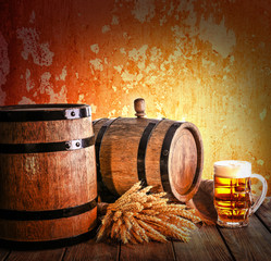 Beer barrel with beer glasses on table on brown background