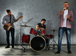 Musicians playing musical instruments and singing songs in a studio