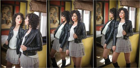 Young woman in black leather jacket and gray short tutu skirt looking into a large mirror. Beautiful curly dark hair girl posing in front of a wall mirror, indoors shot. Fashionable brunette model.