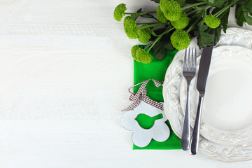 crockery and Cutlery on the cloth near green chrysanthemums on a white wooden table