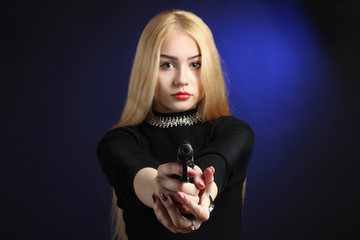 beautiful and serious girl with pistol on dark blue background