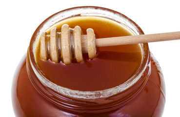 wooden stick on glass jar with honey close up