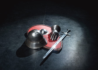 Armor helmet, sword and knight glove lie on a red shield on a gray background