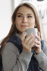 Cropped portrait of woman enjoying a drink at coffee shop