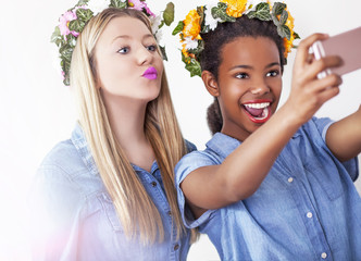 Girls making a selfies, isolated on a white background, studio shoot.