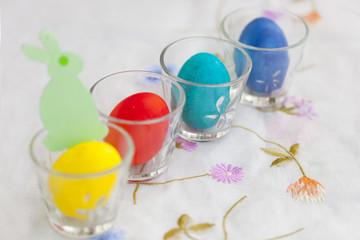 Разноцветные пасхальные яйца в прозрачных стеклянных бокалах с зеленыим бумажным пасхальным кроликом\зайцем