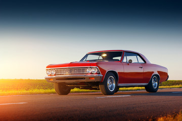 Retro red car stay on asphalt road at sunset Wall mural