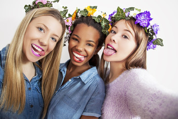 Girls making a selfies, isolated on a white background, studio shoot. Mixed race young girls making a selfie photos and making a funny faces.
