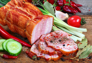 Sliced ham with green and red vegetables on chopping board