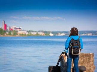 K_S_P. back haired woman blue jeans and jacket backpack blue sea