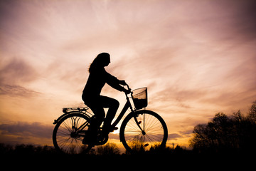 Silhouette of the girl on bicycle - beautiful sunset