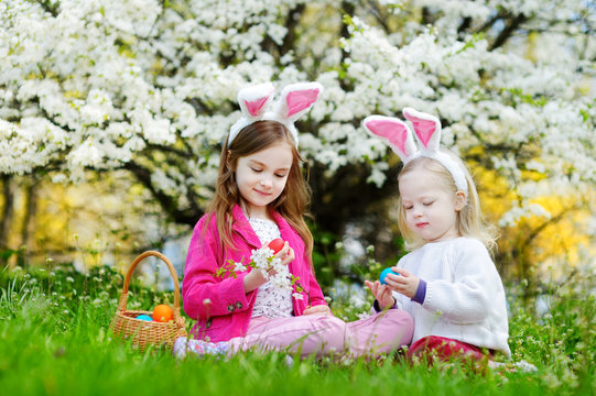 Two adorable little sisters hunting for easter egg in blooming spring garden