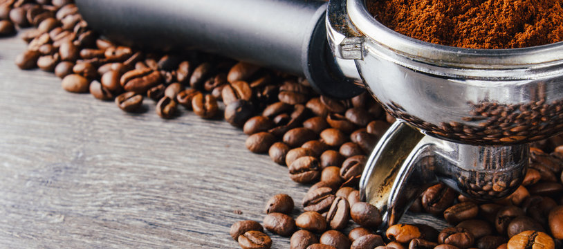 Portafilter and Coffee Beans On Wood Background