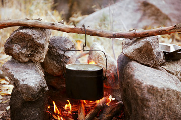 Kettle hanging above fire in the nature