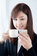 携帯電話を見るビジネスウーマン 朝食 コーヒー
