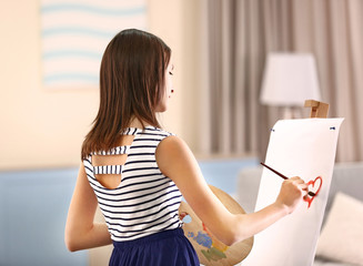 Beautiful girl painting on canvas in room