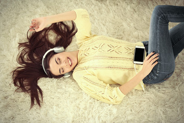 Happy young woman with headphones listening to music on a carpet at home