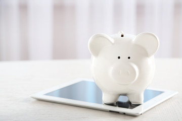 Piggy bank with tablet on table indoors