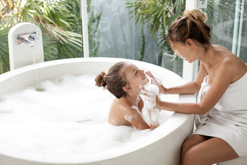 Mother with a child washing in bath
