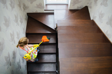 young beautiful woman cleaning wooden stairs by mop