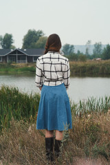 country lady standing against pond on ranch back to viewer