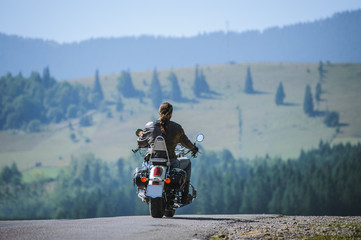Young biker with long hair on mountainous road. Man is riding his custom made travel motorbike on highway. View from the back.