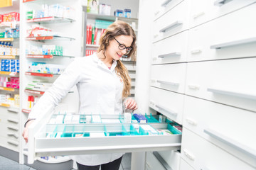 Female pharmacist taking a medicine from a shelf - Doctor opening a drawer in her pharmacy