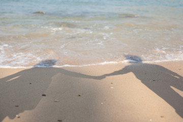 Shadow of young couple holding hands cast on beach sand