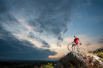 Young man athlete standing on top of a mountain with bicycle and enjoying view, with sky background.