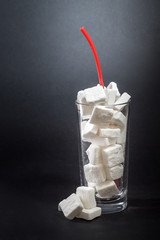 Glass full of sugar cubes with straw