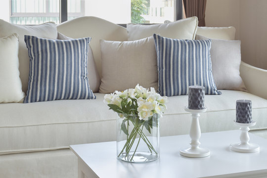 blue striped pillows on a casual sofa and decorative flower in living room