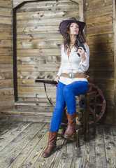 girl cowboy sitting on wooden background wall in the hands of a gun and the gun