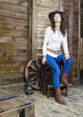 girl cowboy sitting on wooden background wall in hand gun and rifle
