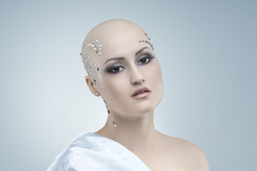 Studio portrait of a beauty bald girl on a sky blue background.Gentle, sensual look. Close-up face