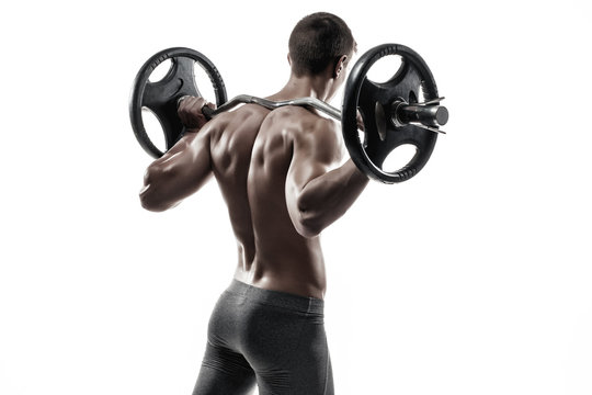 Muscular man holding a barbell on his shoulders, rear view.