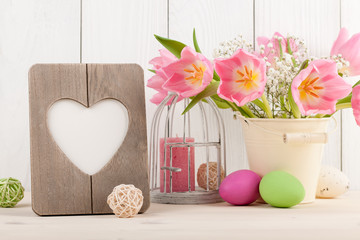 Pink tulips, Easter eggs and heart shaped blank frame