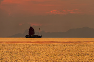 Silhouette of a sailboat floating on the sea on a background of tropical sunset