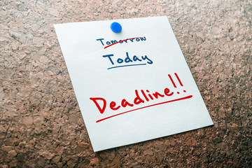 Deadline Reminder For Today With Crossed Out Tomorrow Pinned On Cork Board
