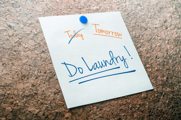 Do Laundry Reminder For Tomorrow With Crossed Out Today Pinned On Cork Board