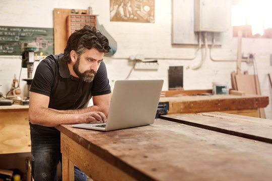 Small business owner in his workshop studio with laptop