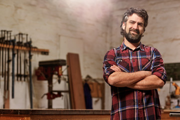 Small carpentry business owner smiling with arms crossed