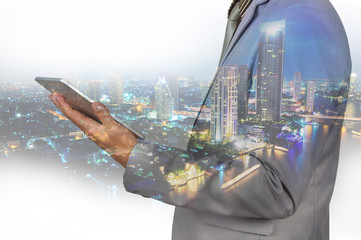Double Exposure image of Businessman use Digital Tablet and City