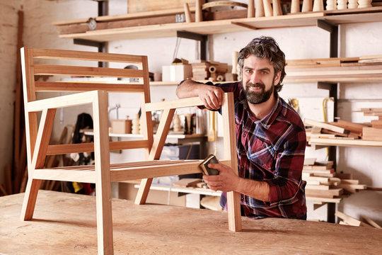Artisan furniture designer sanding a chair in his workshop