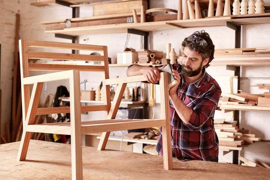 Furniture designer sanding a wooden chair frame