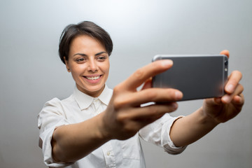 Attractive young woman takes a selfie with a smartphone