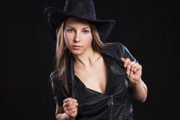 Young beautiful sexy girl leather jacket and  black cowboy hat