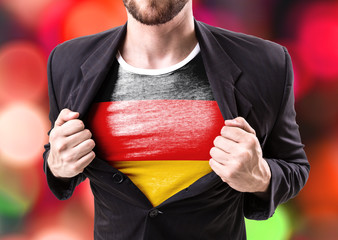 Businessman stretching suit with German Flag with bokeh background