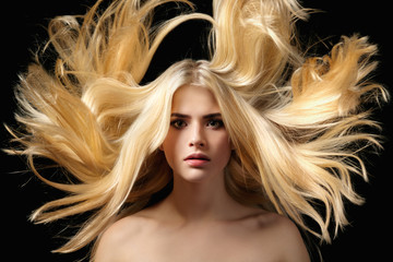 Portrait of beautiful young blonde girl with flying hair