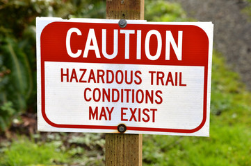 a trail sign stating that hazardous conditions may exist ahead