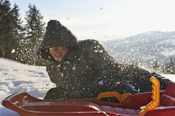 Teen boy falling off his sledge on snow in a winter landscape